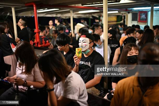 Protesters and other commuters take the Star Ferry to Kowloon after attending a rally in Hong Kong on October 14 calling on US politicians to pass a...