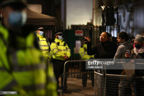 Protesters and police officers stand outside Scotland Yard during a protest criticising the actions of the police at last night's vigil on March 14,...