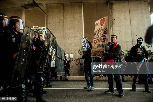 Protesters and refugees are blocked by police at the entrance of the jungle Some sing and dance and hold placards in Calais France October 1st 2016 A...