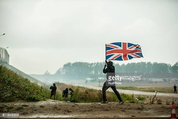 Protesters and refugees are blocked by police at the entrance of the jungle A refugee holds an English flag against the water cannon in Calais France...