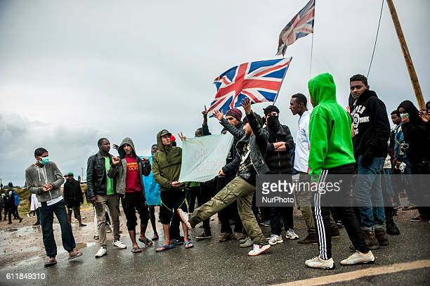 Protesters and refugees are blocked by police at the entrance of the jungle English flags waved by refugees in Calais France October 2016 1s...