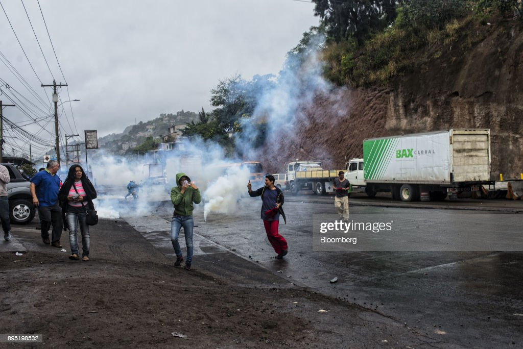 Protesters and residents of the Villanueva community run away from the tear gas during protests against the presidential election of Juan Orlando Hernandez in Tegucigalpa, Honduras, on Monday, Dec. 18, 2017. Honduran electoral authorities declared incumbent Hernandez the winner of the Nov. 26 presidential vote after three weeks in which the nation slid into chaos as ballots were counted and recounted. Photographer: Juan Carlos/Bloomberg via Getty Images