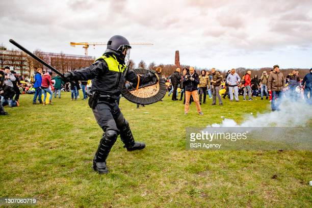 Protesters and riot police are seen during a protest on the Malieveld against the coronavirus policies and the government on March 14, 2021 in The...