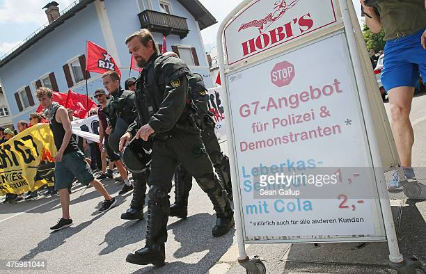 Protesters and riot police marching through the city center walk past a sign outside a snack bar reads 'Stop G7 Offer for Police and Demonstrators...
