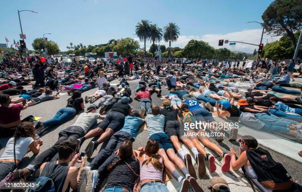 Protesters and supporters of Black Lives Matter lie in the street as they block an intersection outside the Federal Building on busy Wilshire Blvd as...
