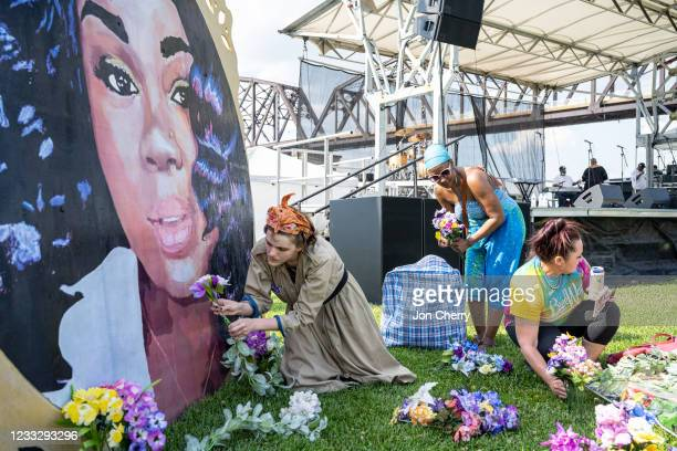 """Protesters and volunteers prepare a Breonna Taylor art installation by laying posters and flowers before the """"Praise in the Park"""" event at the Big..."""