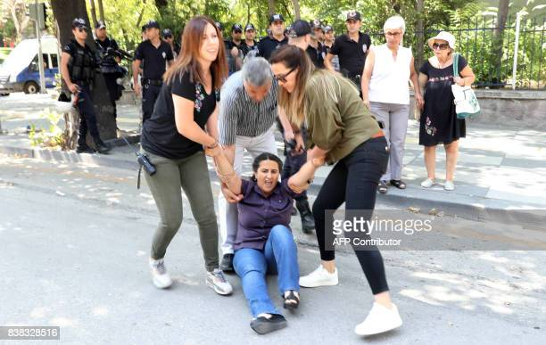 Protesters are detained by riot police as they protest against the detention of hungerstriking teacher Semih Ozakca and literature professor Nuriye...