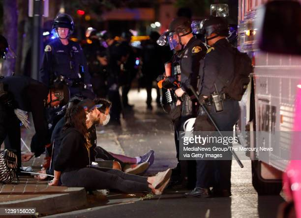 Protesters are detained for breaking curfew by San Jose Police officers before being loaded into Santa Clara County Sheriffs vehicles while...