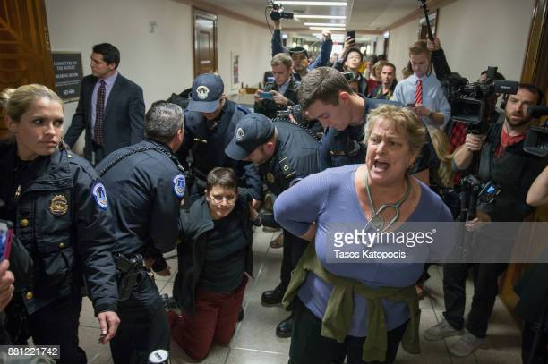 Protesters are detained near the full Senate budget committee markup of the tax reform legislation on Capital Hill November 28 2017 in Washington DC...