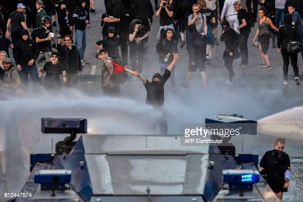 TOPSHOT Protesters are doused with water during the 'Welcome to Hell' rally against the G20 summit in Hamburg northern Germany on July 6 2017 Leaders...