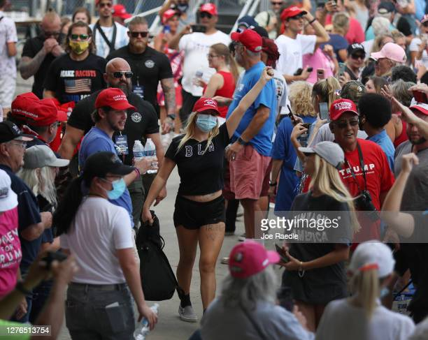 A protesters are escorted out before the arrival of President Donald Trump for his 'The Great American Comeback Rally' at Cecil Airport on September...