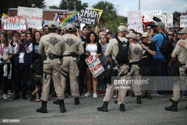 Protesters are held behind a line of police as they react to white nationalist Richard Spencer who popularized the term ÔaltrightÕ speech at the...