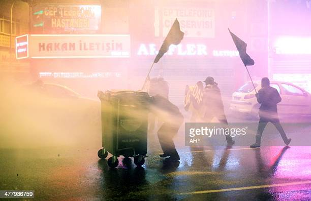 Protesters are hit by water cannon during clashes with riot police in Kadikoy on the Anatolian side of Istanbul on March 11 2014 Turkish riot police...