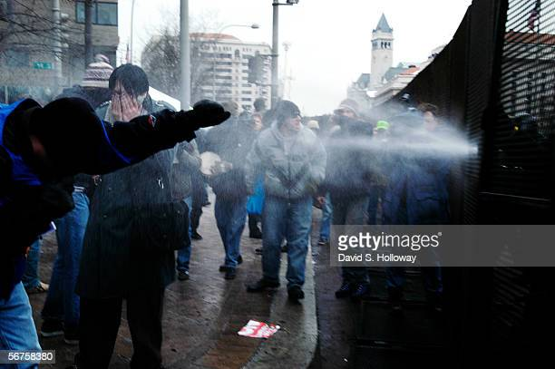 Protesters are pepper sprayed from police behind a security fence along the Pennsylvania Ave inauguaral parade route in Washington DC on January 20...