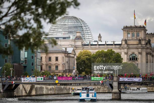 Protesters are pictured during the protest of 'Extinction Rebellion' on the bridge 'Marschallbruecke' on October 09, 2019 in Berlin, Germany....