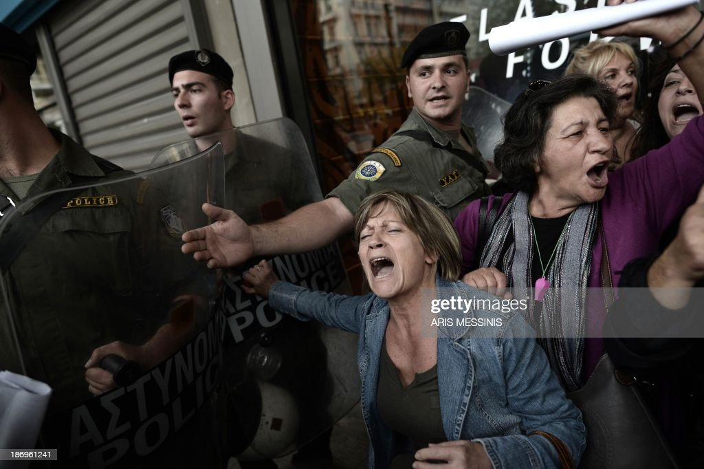 Protesters are pushed back from the riot police as EU and IMF officials escorted out from the emergency exit of the Greek Finance Ministry after their meeting with the Greek Finance Minister in Athens on November 5, 2013. Mission chiefs from the European Commission, the International Monetary Fund and the European Central Bank on November 5 began a new round of talks with members of the debt-wracked Greek government.