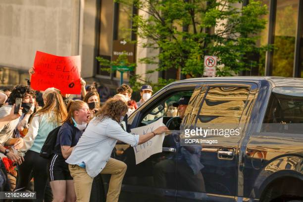 Protesters are seen attacking a man in a Ford F-150 after running over a protester's foot while attempting to pass through the protest crowd during...