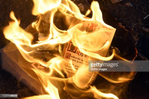 Protesters are seen burning a page of the Spanish Constitution during the protest Hundreds of people demonstrate against the presence of the King of...