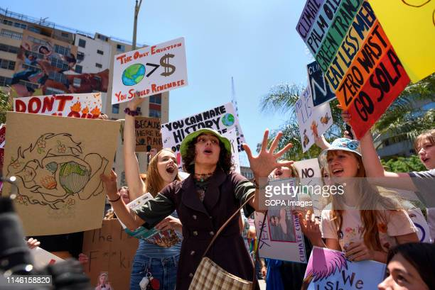 Protesters are seen during a climate change demonstration shouting slogans while holding placards Students and environmental activists participate in...