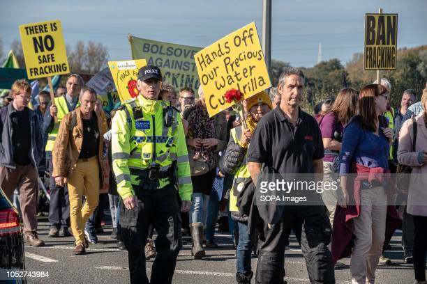 Protesters are seen during the march towards the frack site with a police officer seen walking alongside them Protesters from the United Kingdom...