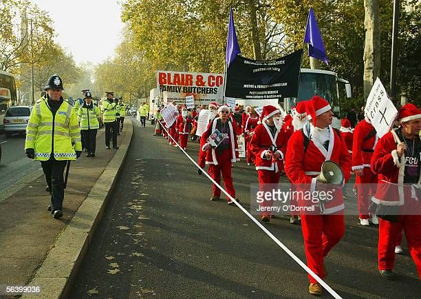 Protesters are seen flanked by police during a Fathers 4 Justice christmas campaign march, from the Church of England headquaters in Westminster to...