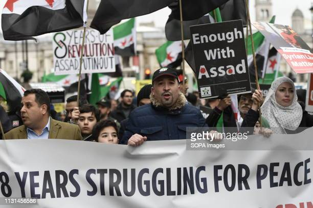 Protesters are seen holding a banner and placard during the 8th Anniversary of the Syrian Revolution protest Syrians marched from Paddington Green to...