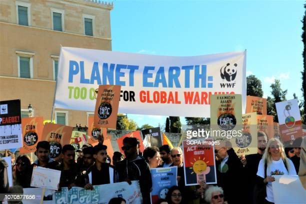 Protesters are seen holding a banner and placards during a protest calling for increased efforts to stop climate change