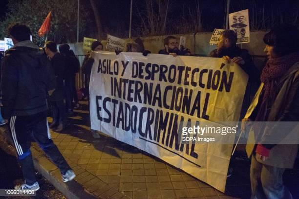 Protesters are seen holding a banner during a protest in front of the Immigration Detention Centre in Madrid Protesters were demanding the closure of...
