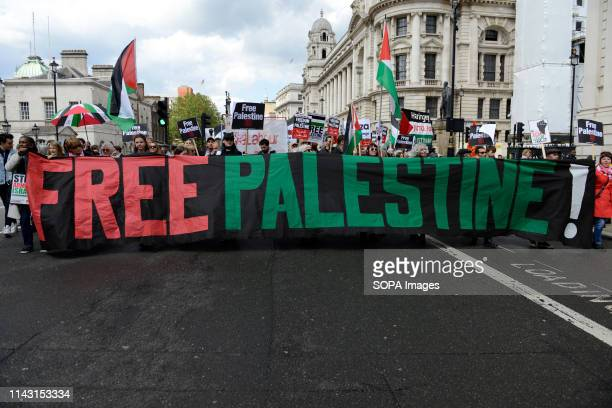 Protesters are seen holding flags placards and a banner that says free Palestine during the demonstration Palestinian human rights activist Ahed...