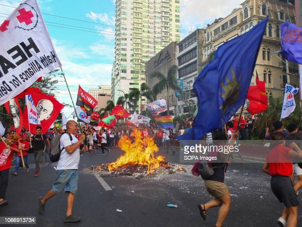 Protesters are seen holding flags while running around the burning effigy of President Duterte during the protest Leftist groups stage Bonifacio Day...