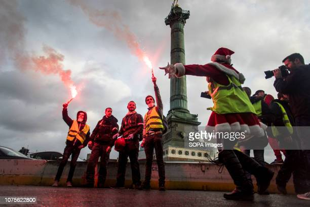 Protesters are seen holding flares with a woman dressed like Santa Calus in La Bastille square during the demonstration. Yellow vest protesters went...