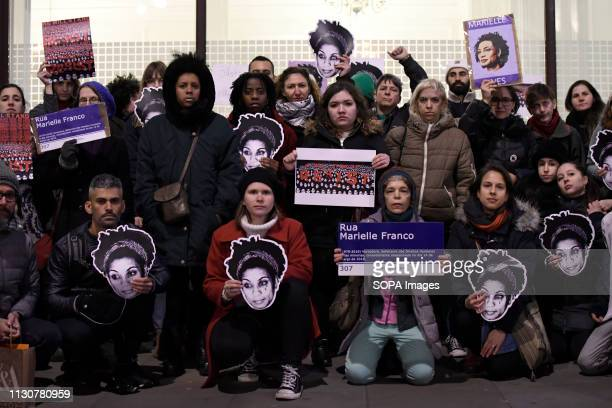 Protesters are seen holding placards and masks depicting the image of Marielle Franco outside the Brazil embassy in London during the vigil...