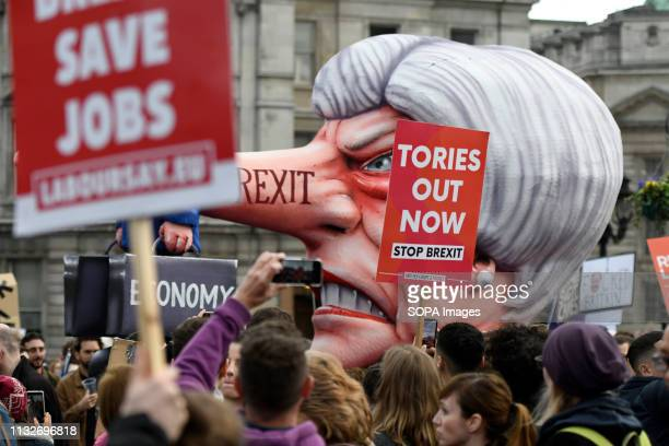 Protesters are seen holding placards while An effigy of Prime Minister Theresa May passes by Trafalgar Square during the demonstration Over a million...