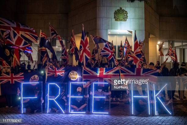 Protesters are seen holding up Union Jacks and LED Lit Letters which reads Free HK in front of the British Consulate General in Central in Hong Kong...