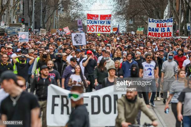 Protesters are seen marching holding banners on August 21, 2021 in Melbourne, Australia. Anti-lockdown protesters gathered despite current COVID-19...