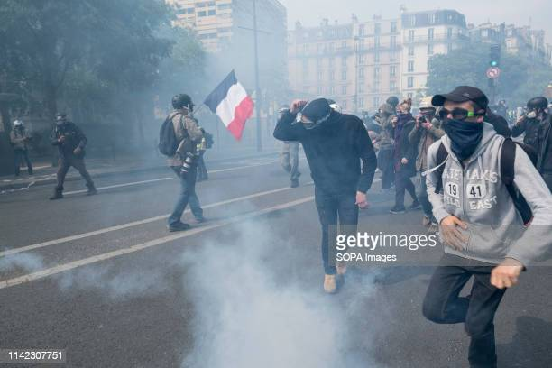 Protesters are seen running for cover amidst tear gas smoke during the May Day protests in Paris May Day is a public holiday celebrated normally on 1...