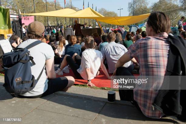 Protesters are seen seated while listening to speeches during the protest Climate change activists from the Extinction Rebellion camped at the Marble...