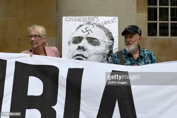 Protesters are seen sitting next to a placard with the photo of Colombian President Ivan Duque in London Colombians gathered outside the BBC in...