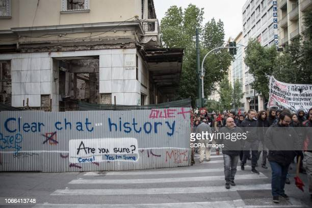 Protesters are seen walking next to a wall with slogans during the protest Hundreds of students protest against the rise of fascism and racism in...