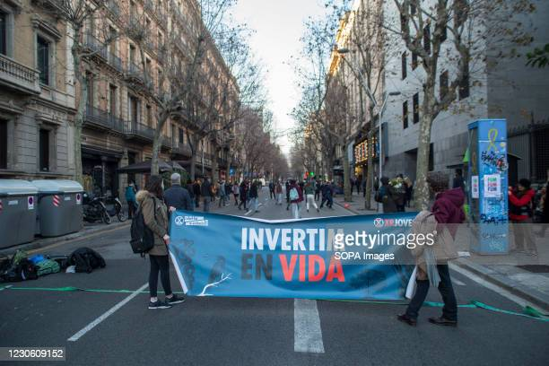 """Protesters are seen with a sign that reads """"We invest in life."""" The Barcelona unit of the international movement against the climate and ecological..."""