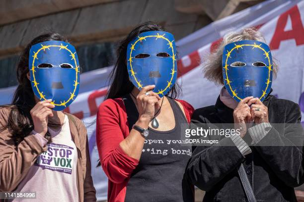 Protesters are seen with masks surrounded by barbed wire in reference to immigration detention centres and border crossings during a demonstration...