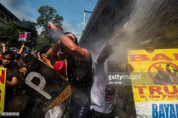Protesters are soaked as they clash with riot police as they march the streets of Manila during the start of the ASEAN meetings between heads of...