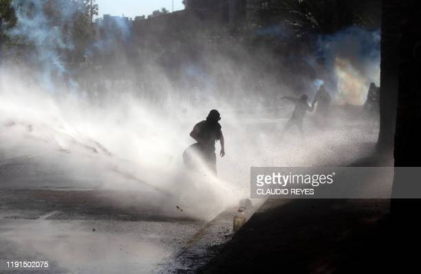 Protesters are sprayed with water during clashes with riot police on the first protest of the year against the government of President Sebastian...