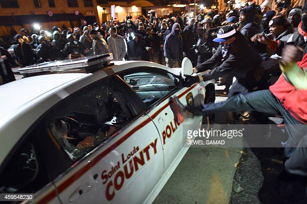 Protesters attack a police car during clashes following the grand jury decision in the death 18yearold Michael Brown in Ferguson Missouri on November...