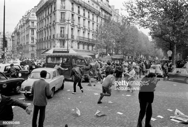 Protesters attack a police vehicle on Boulevard Saint Germain during the MayJune 1968 events in France / AFP PHOTO / Jacques MARIE