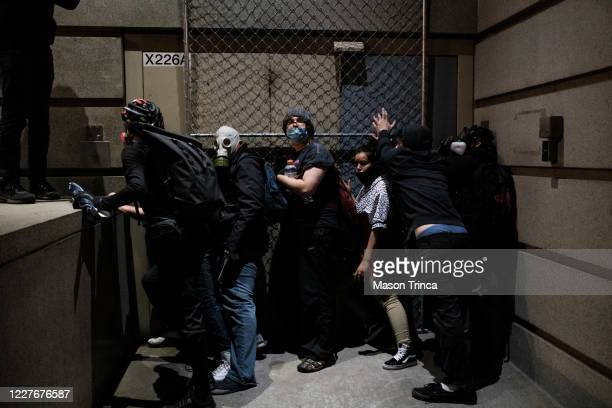 Protesters attempt to barricade a door to the Multnomah County Justice Center on July 17 2020 in Portland Oregon Federal law enforcement agencies...
