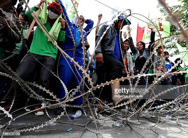 Protesters attempt to dismantle barbed wire barricades during a protest demanding higher wages on October 31 2013 in Surabaya Indonesia Several...