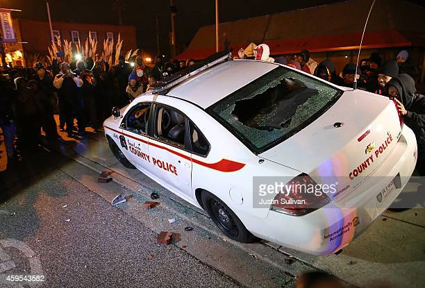 Protesters attempt to tip over a police car during a demonstration on November 24 2014 in Ferguson Missouri A St Louis County grand jury has decided...
