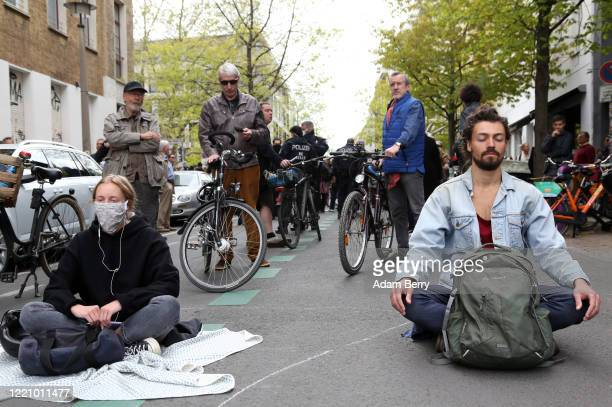 Protesters attempting to show they are peaceful meditate as they demonstrate against restrictions on public life designed to stem the spread of the...