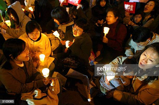 Protesters attend a candle light rally to oppose the parliamentary impeachment of President Roh Moo-Hyun on March 17, 2004 in Seoul, South Korea....